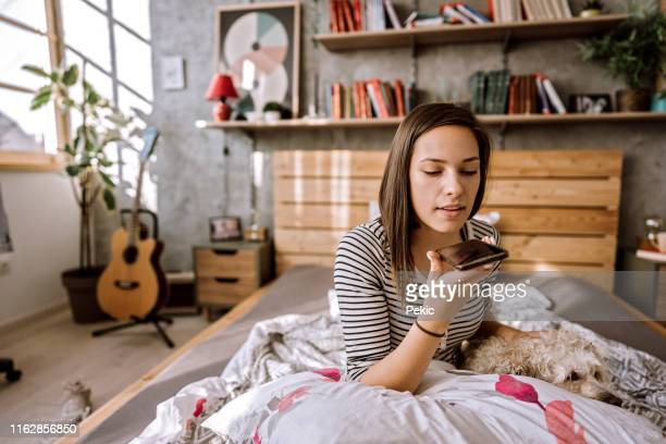young woman sending voice messages - speech recognition stock pictures, royalty-free photos & images