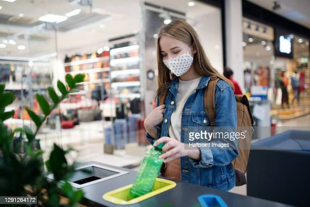 young woman separating waste in bin indoors in shopping center at christmas, coronavirus concept. - recycling bin stock pictures, royalty-free photos & images