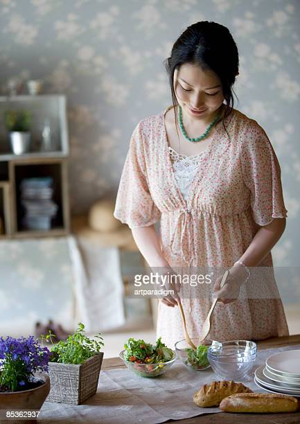 Young woman serving a salad