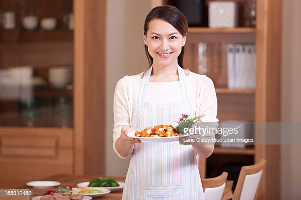 Young woman serving Chinese dishes