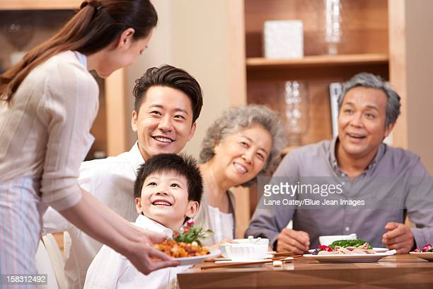 Young woman serving Chinese food for the whole family