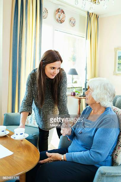 Young woman serving coffee to grandmother at home