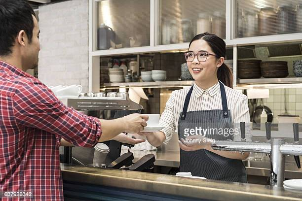 Young woman serving coffee to male customer