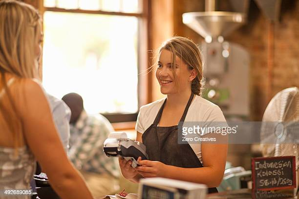 Young woman serving customer in coffee shop