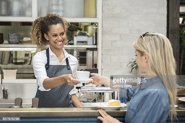 Young woman serving female customer in cafe