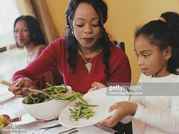 young woman serving girl (6-8) at dinner table - thanksgiving dog stock photos and pictures