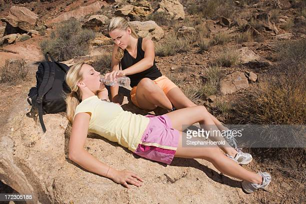 Young woman serving water to her friend who is dehydrated