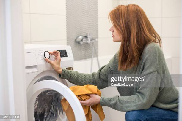 junge frau, die einstellung einer waschmaschine - wäsche stock-fotos und bilder