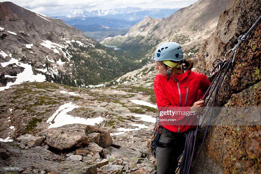 Young woman setting an anchor and belaying her partner : Stock Photo