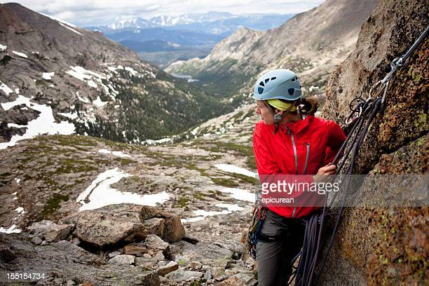 Young woman setting an anchor and belaying her partner