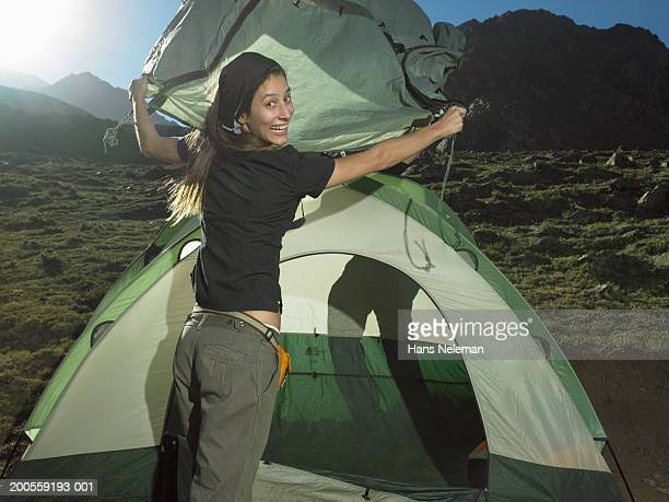 Young woman setting up tent on mountain, smiling, portrait