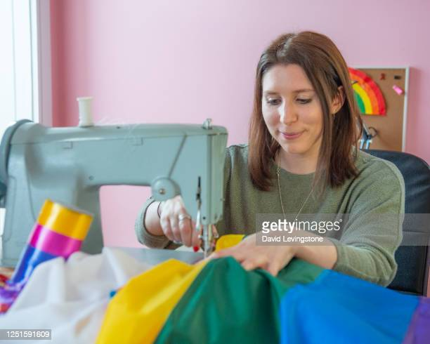 young woman sewing a rainbow pride flag in support of lgbtqi+ pride at home. - mid adult women stock pictures, royalty-free photos & images