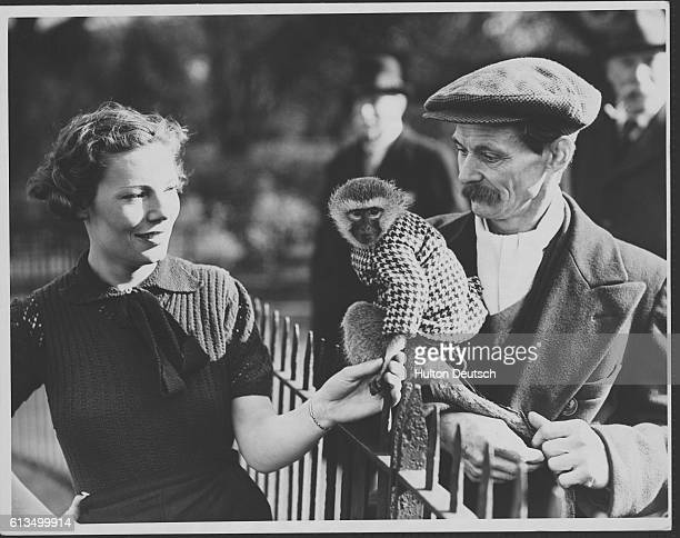 A young woman shakes hands with a monkey while training in London's Battersea Park England 1938