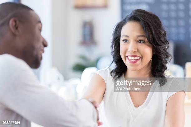 Junge Frau schüttelt Hände mit unkenntlich Mann im Café
