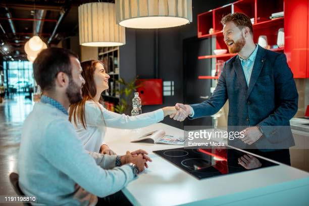 young woman shaking hands with a sales assistant in a house improvement store - interior design foto e immagini stock