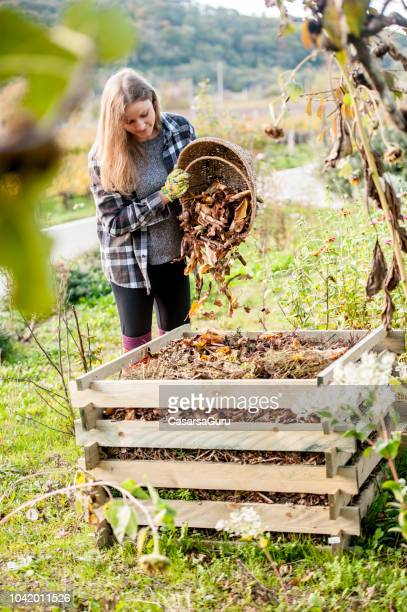Young Woman Shaking Leaves Out of Basket to Compost