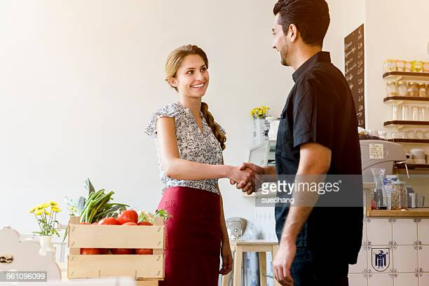 Young woman shaking mans hand