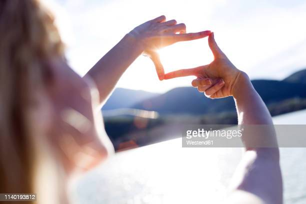 young woman shaping frame with her fingers at sunset - molding a shape stock pictures, royalty-free photos & images