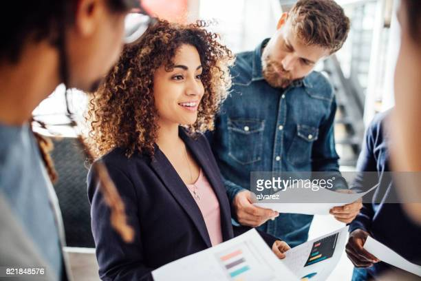 Young woman sharing business reports with colleagues.