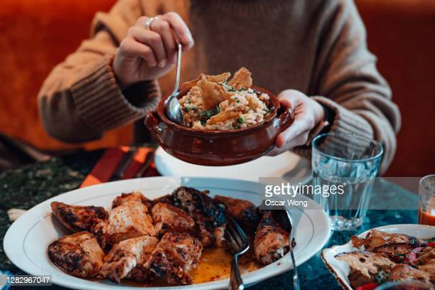 young woman sharing food with friends at restaurant - traditionally portuguese stock pictures, royalty-free photos & images