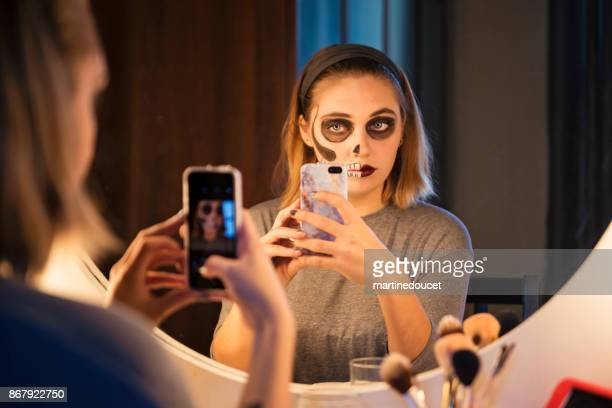 Young woman sharing her Halloween makeup on social media