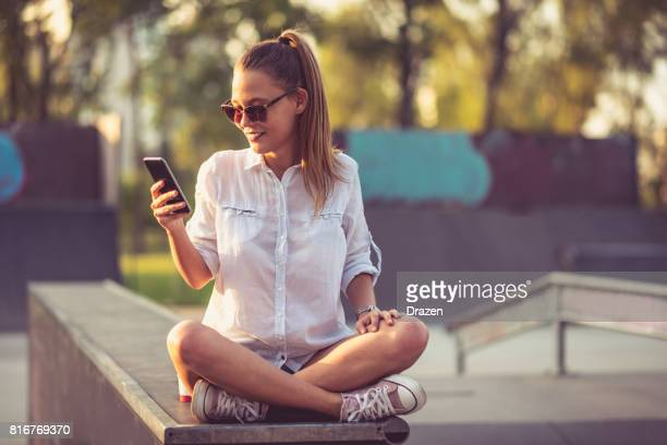 Young woman sharing images from skateboarding park on social networks