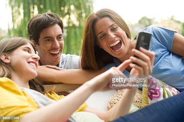 Young woman sharing photos on smartphone with friends