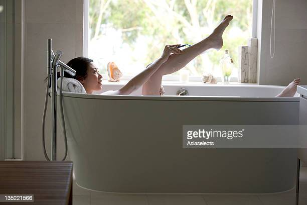 Young woman shaving while taking a bath.