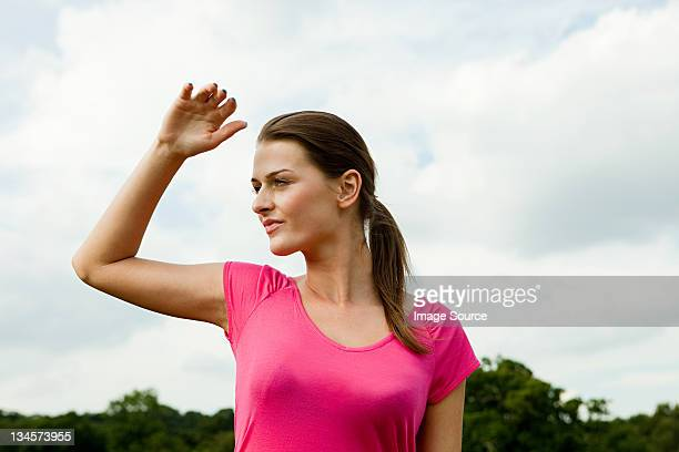 Young woman shielding eyes from the sun in the countryside