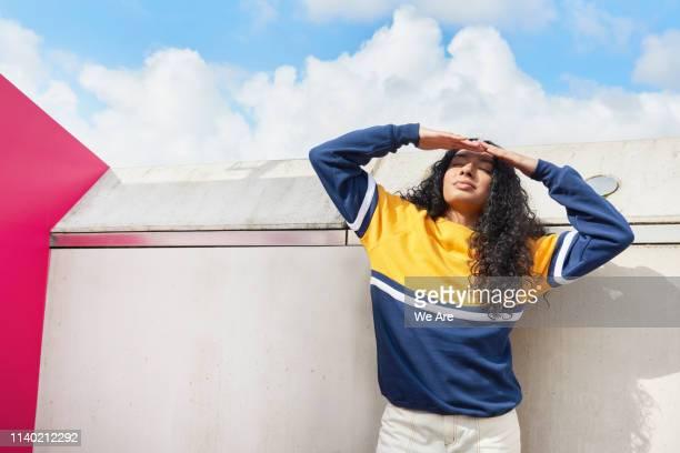 young woman shielding eyes from the sun - leuchtende farbe stock-fotos und bilder