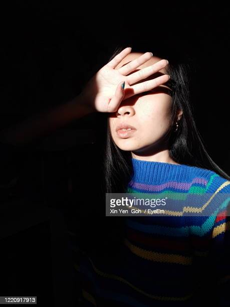 young woman shielding eyes - hiding stock pictures, royalty-free photos & images