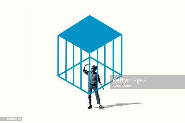 young woman shielding eyes under blue cage - 檻 ストックフォトと画像