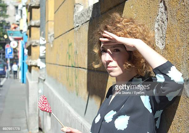 Young Woman Shielding Eyes While Holding Lollipop By Wall