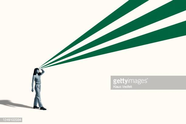 young woman shielding eyes with green rays - motivation stock pictures, royalty-free photos & images