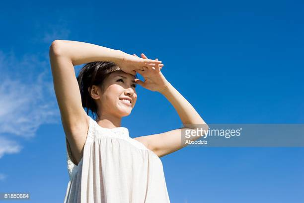 Young woman shielding her eyes and looking at view