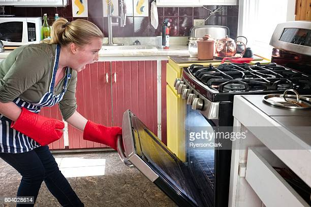 Young woman shocked at oven fire, rural kitchen.
