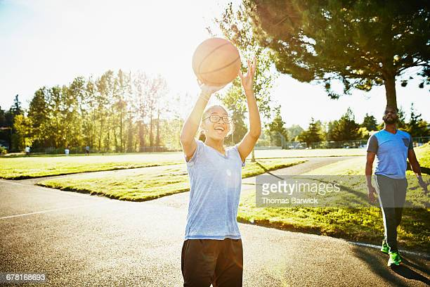 Young woman shooting jump shot on basketball court