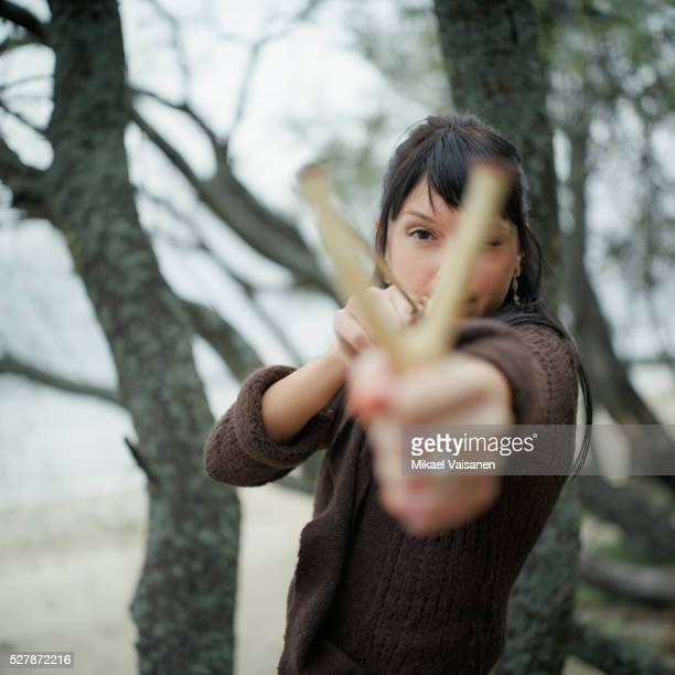 Young Woman Shooting Slingshot in Woods