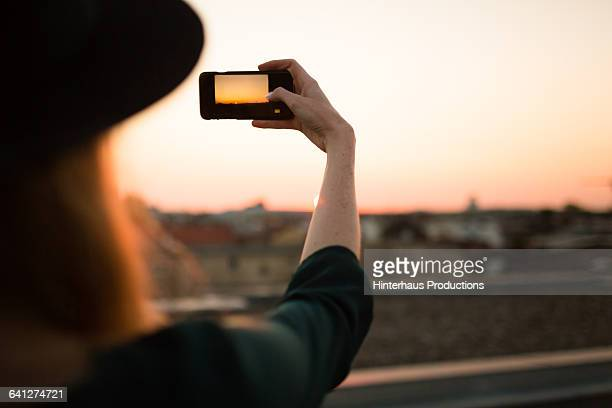 Young woman shooting sunset with her smart phone