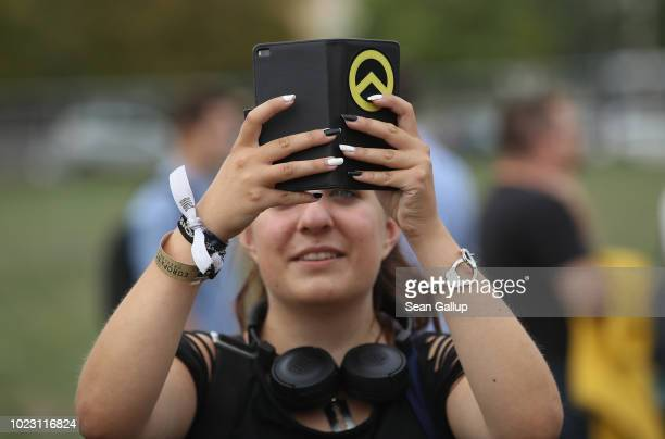 A young woman shoots a video clip with a smartphone decorated with the logo of the Identitarian Movement at a gathering entitled Europa Nostra and...