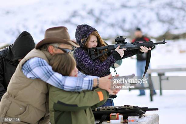 Young woman shoots an assault style rifle while a grandfather teaches his grandson how to shoot a shotgun pistol at the shooting range.