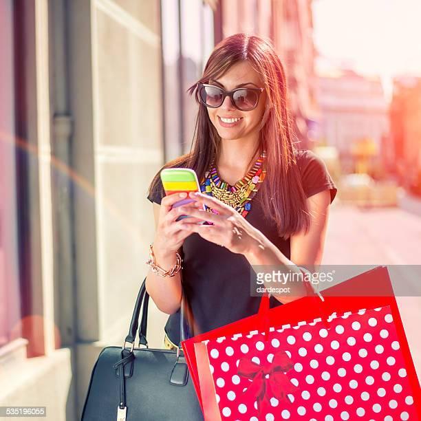 Junge Frau Einkaufen und mit Handy