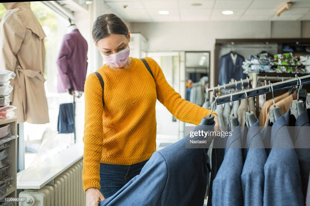 Young woman shopping at the time of virus wearing protective mask : Stock Photo