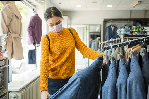 Young woman shopping at the time of virus wearing protective mask 1220990167
