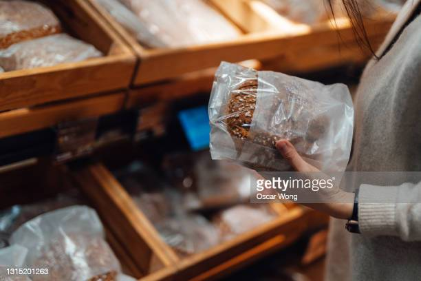 young woman shopping bread in supermarket - bread stock pictures, royalty-free photos & images