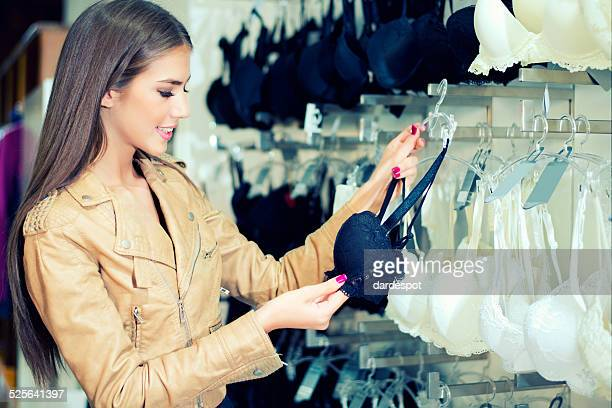 young woman shopping for bra. - lingerie stock pictures, royalty-free photos & images