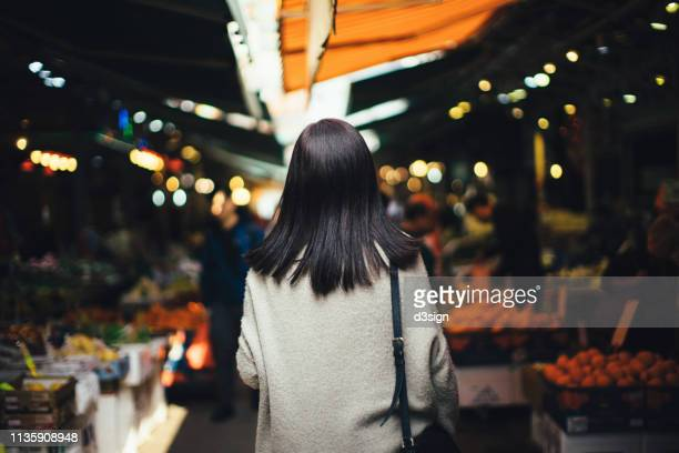 young woman shopping for fresh fruits and local produces in a local fruit market - markt stockfoto's en -beelden