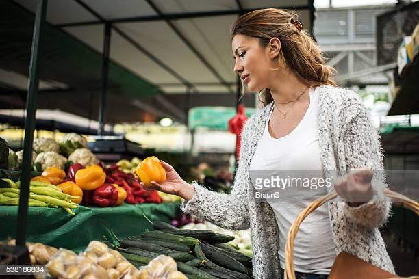 Junge Frau einkaufen für Lebensmittel auf farmer's market.