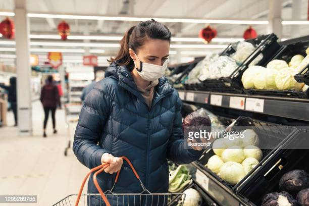 young woman shopping for healthy food in supermarket with protective facemask - supermarket stock pictures, royalty-free photos & images