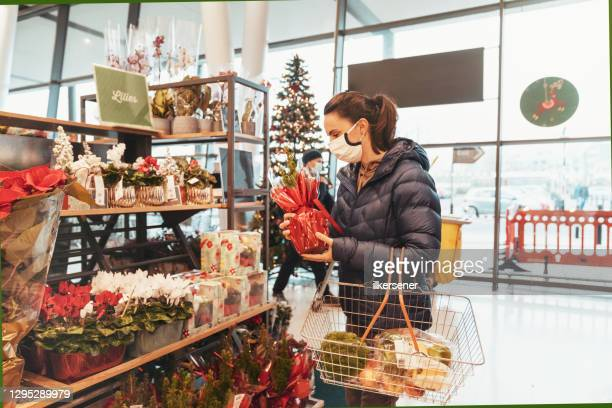 young woman shopping for healthy food in supermarket with protective facemask - christmas stock pictures, royalty-free photos & images